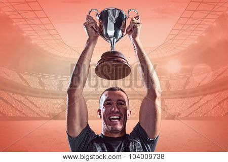 Portrait of successful rugby player holding trophy against orange