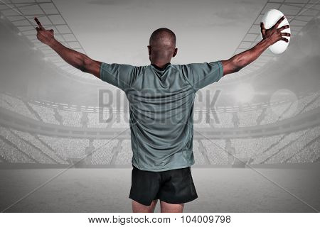 Rear view of athlete with arms raised holding rugby ball against grey vignette