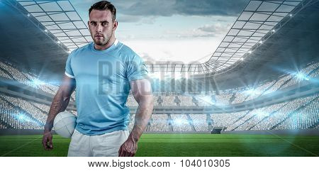 Rugby player looking at camera against rugby stadium