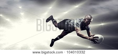 Sportsman jumping for catching rugby ball against spotlights