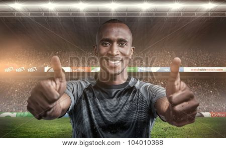 Portrait of confident athlete smiling and showing thumbs up against rugby fans in arena