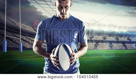 Rugby player holding ball against rugby stadium