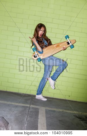 Beautiful Long-haired Lady With A Wooden Longboard Near A Green Brick Wall