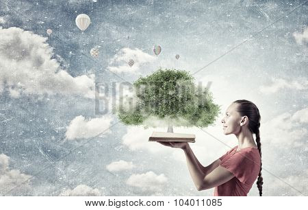 Young woman in red dress holding opened book with green tree