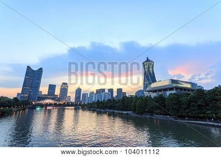 skyscrapers of a modern city along a river at dusk