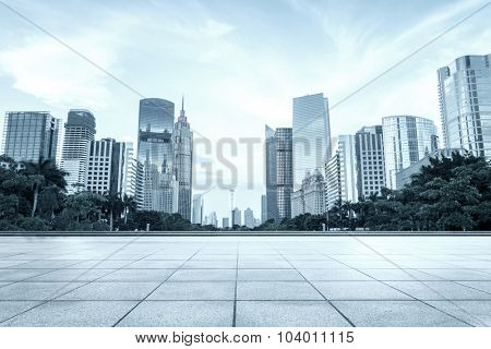 empty, modern square and skyscrapers under cloudy sky