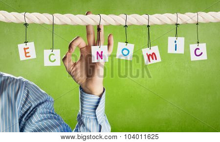 Word economic composed of cards hanging on rope and ok gesture