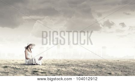 Young lady sitting on grass with laptop on knees