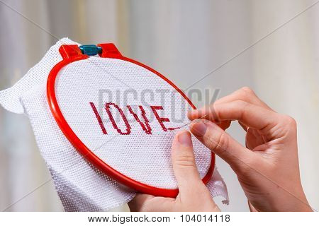 Hands Embroidering A Word Love
