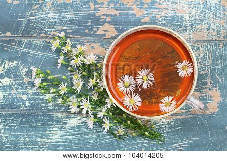 Chamomile tea in glass with fresh chamomile flowers on rustic surface