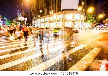 crowded road with zebra crossing and gymnasium in modern city at night