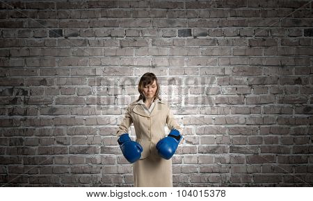 Young businesswoman in blue boxing gloves competition ready