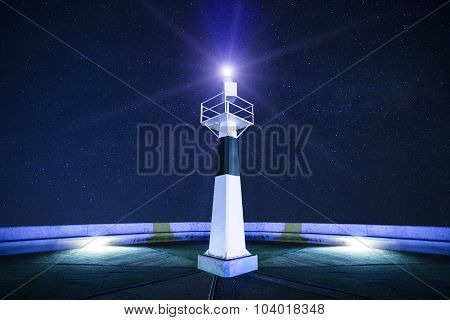 Lighthouse at starry night with searchlight beam