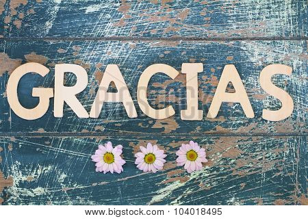 Gracias (which means thank you in Spanish) written on rustic wooden surface and pink daisies