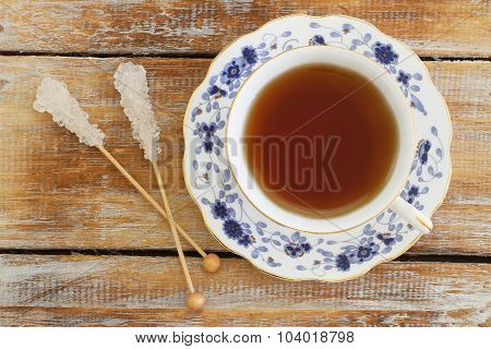 Tea in vintage porcelain cup and two sugar sticks on rustic wooden surface