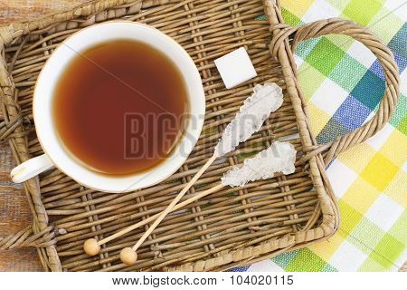 Black tea in porcelain cup and white sugar on wicker tray
