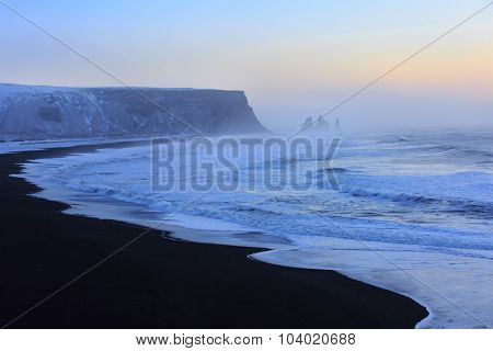 Landscape with beach of black sand and   the sea stacks in the background at sunrise. Reynisdrangar , near Vik, Iceland