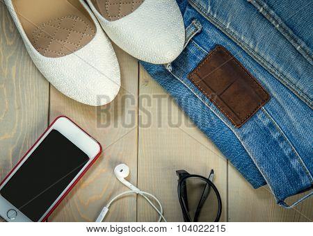 White woman shoes, smart, jeans, headphones and sunglasses on a wooden background