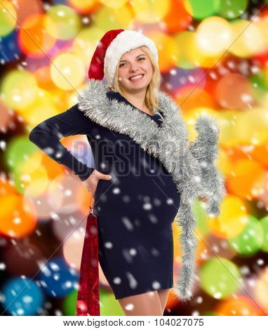 pregnant woman in santa hat on christmas colorful background with shopping bag and snow
