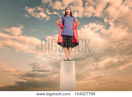 little girl wearing a superhero costume on a pedestal