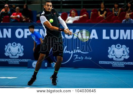 KUALA LUMPUR, MALAYSIA - SEPTEMBER 30, 2015: Nick Kyrgios of Australia attempts a backhand return in his match at the Malaysian Open 2015 Tennis tournament held at the Putra Stadium, Malaysia.
