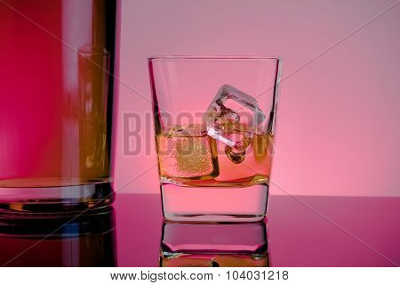 One Glass Of Whiskey With Ice Cubes Near Bottle On Table With Reflection, Lights Disco Atmosphere