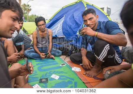 KOS, GREECE - SEP 28, 2015: War refugees playing cards near the tents. More than half are migrants from Syria, but there are refugees from other countries -Afghanistan, Pakistan, Iraq, Iran, Mali.