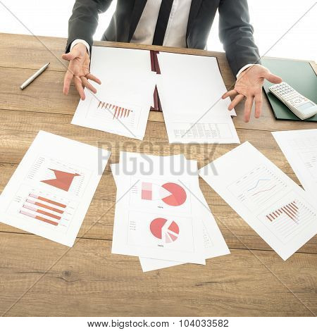 Busy Financial Adviser Working At His Business Desk With Many Documents, Charts And Reports Placed A