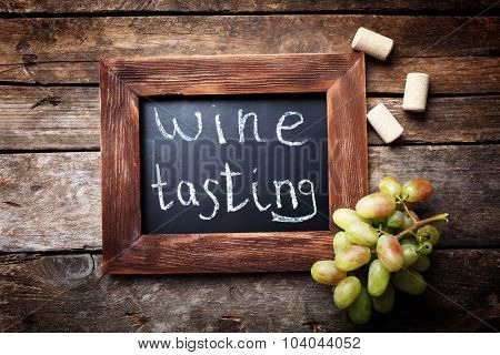Square frame with grape on wooden background