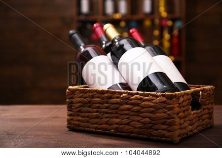 Wattled basket with labeled bottles of wine on unfocused dark background