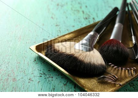 Make up brushes on wooden table closeup