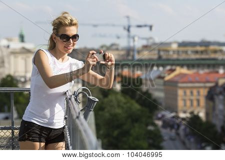 Attractive young woman takes photo on smartphone from the observation deck.