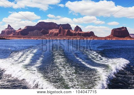 Foamy trace of a motor boat crosses the emerald waters. In distance the coast of red sandstone. Lake Powell on the Colorado River