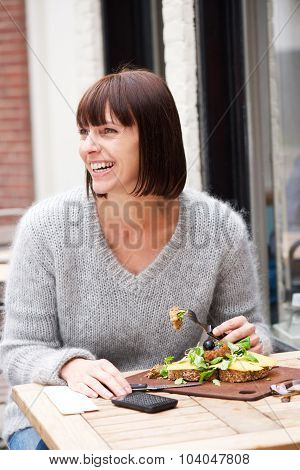 Smiling Woman Sitting At Table Eating Food