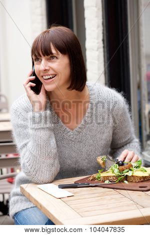 Smiling Woman Eating Food And Talking On Mobile Phone