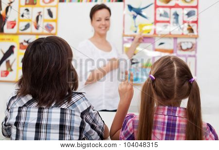 Kids in elementary science class with their teacher - closeup, focus on the child hand