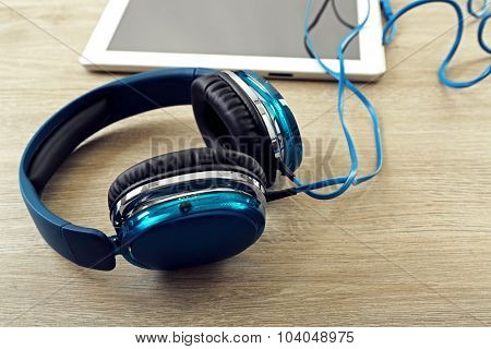 Headphones with tablet on wooden table close up