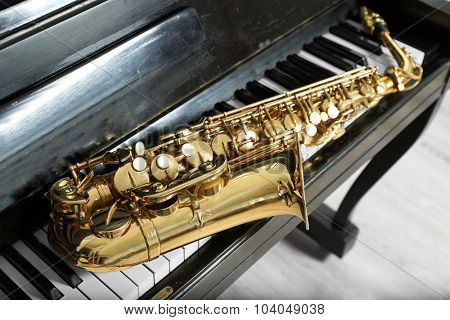 Saxophone on piano keys, closeup