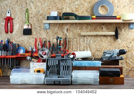 Set of tools in workshop on plywood background