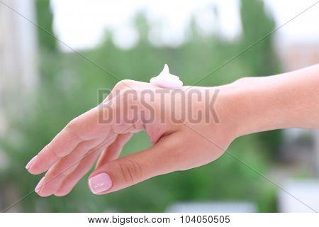 Women applying cream on her hands outdoor