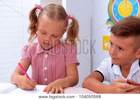 Little girl drawing at the desk in classroom