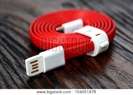 Red USB cable on wooden table
