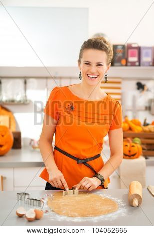 Woman Cutting Out Halloween Biscuits In Kitchen