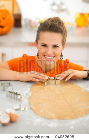 Woman Cutting Out Halloween Cookies With Pastry Cutter