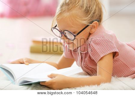 Little girl reading book in the room