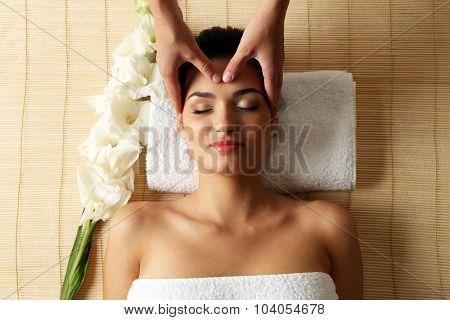 Young woman in beauty spa salon enjoying head massage