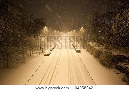 Dense snowfall and empty road at night
