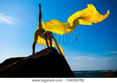 Silhouette of the sports girl with yellow fabric against the sky