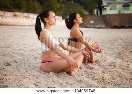 Women in Yoga meditation pose at amazing sunset