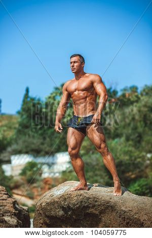 Man Athlete on a rock by the sea against the sky